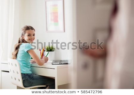 schoolgirl doing homework and mother entering room stock photo © dolgachov