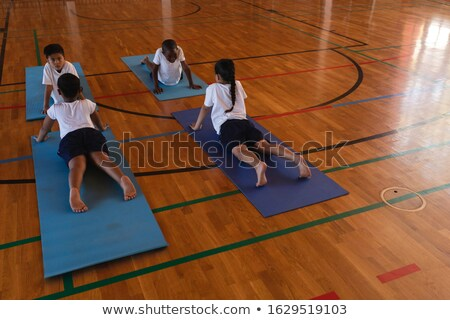 High angle view of schoolkids doing yoga on a yoga mat in school gymnasium Stock photo © wavebreak_media