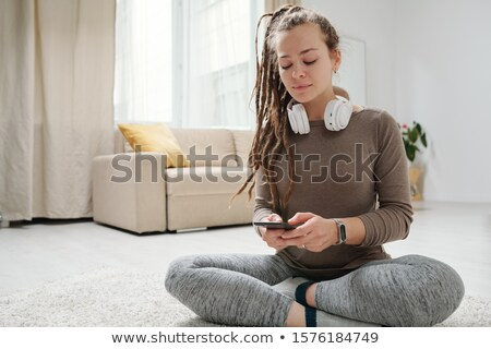 Girl with dreadlocks scrolling in smartphone while sitting with crossed legs Stock photo © pressmaster