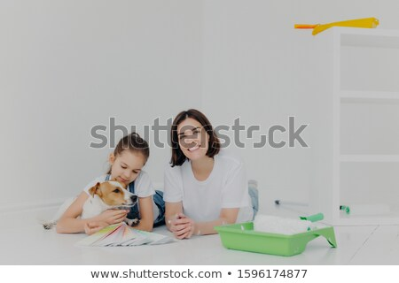 Photo of mother, daughter and pedigree dog lie on floor, take break after painting walls, surrounded Stock photo © vkstudio