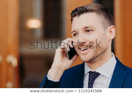 Sideways shot of handsome young male talks in roaming via cell phone, has positive expression, looks Stock photo © vkstudio