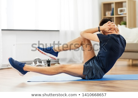 man making bicycle crunch exercise at home Stock photo © dolgachov