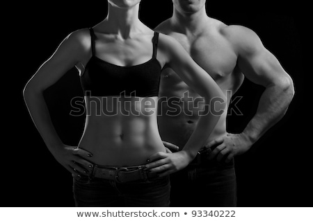 Stock photo: Muscular female torso on black background