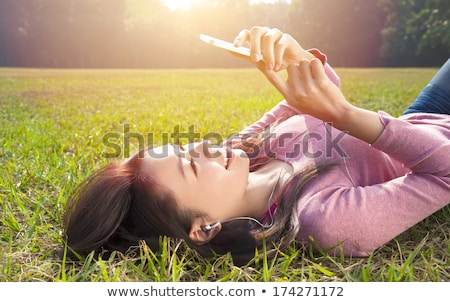 Girl With mobiles resting on the grass  Stock photo © OleksandrO