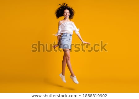 Stock photo: Attractive girl in jeans mini skirt. Isolated