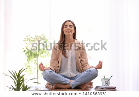 Businesswoman meditating in lotus posture Stock photo © stockyimages