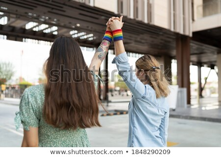 Rear view of a lesbian couple standing with holding hands Stock photo © bmonteny