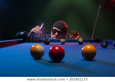 Man playing pool in a club smoking a cigarette Stock photo © stryjek