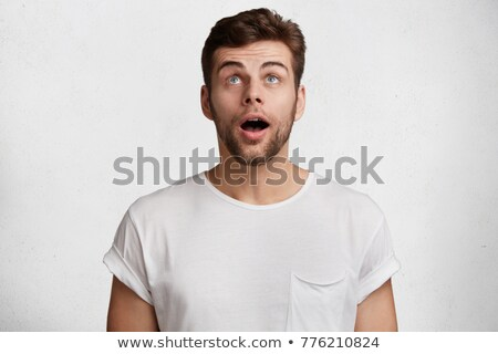 amazed young casual man is looking up to something stock photo © feedough
