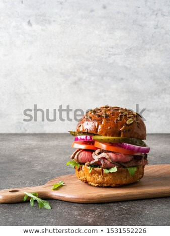 Tasty cut meat steak with greens and arugula on a wooden plate a stock photo © Yatsenko