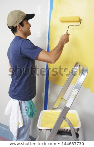 Young hispanic house painter holding paint roller. Stock photo © RAStudio