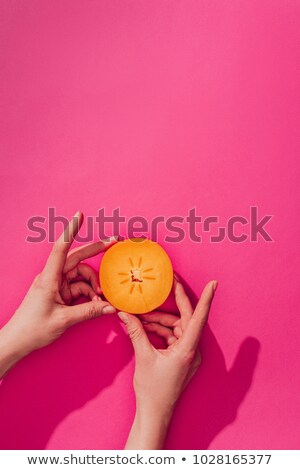 cropped image of woman holding persimmon piece on pink stock photo © lightfieldstudios