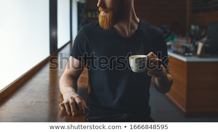 A man is sitting in the office at the table and drinking coffee from a glass. Stock photo © Traimak