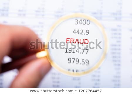 Man Examining Fraud Word On Financial Report Stock photo © AndreyPopov