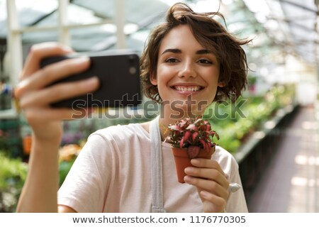 Bonitinho mulher jardineiro em pé plantas estufa Foto stock © deandrobot