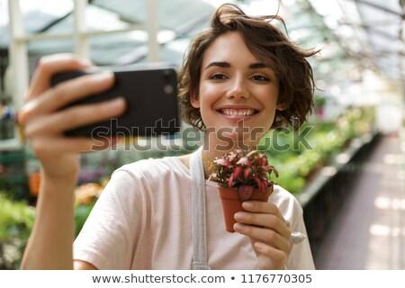 Cute woman gardener standing over plants in greenhouse. stock photo © deandrobot