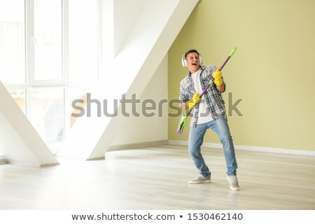 man in headphones cleaning floor by mop at home stock photo © dolgachov