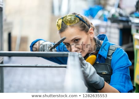 Stock photo: Woman metalworker checking the accuracy of her work