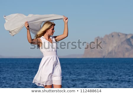 happy woman with shawl waving in wind on beach Stock photo © dolgachov