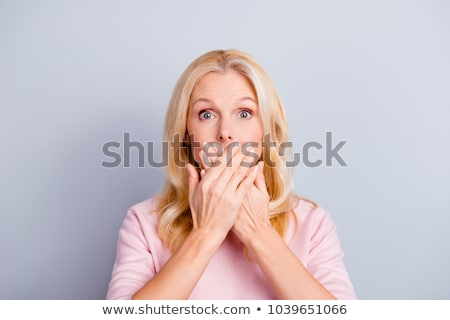 Amazed lovely woman covering mouth with hand stock photo © studiolucky