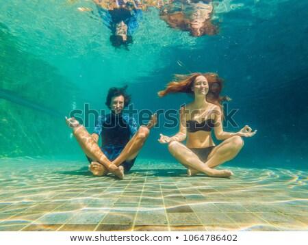 Fiatalember fekete bikini jóga pozició vízalatti Stock fotó © galitskaya