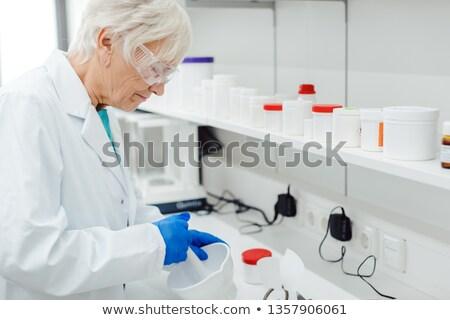 Pharmacist woman mixing some drug or medicine in laboratory Stock photo © Kzenon