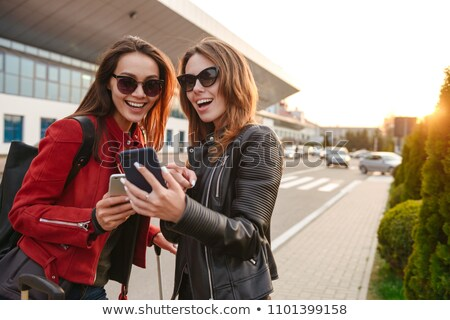 image of two joyous european women wearing sunglasses looking at stock photo © deandrobot