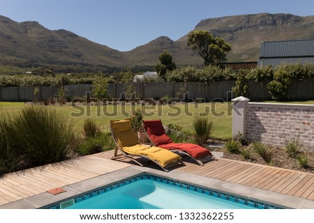 Stock photo: Empty sun lounger chairs placed next to the swimming pool at the backyard of home