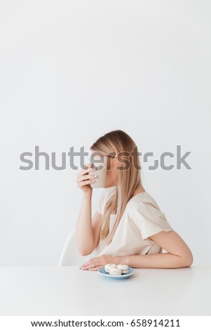 Lady sitting isolated near sweeties covering face with coffee. Stock photo © deandrobot