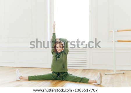 Full length shot of cheerful redhead woman raises hands, does splits, stretches muscles, sits on flo Stock photo © vkstudio