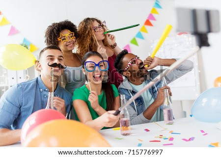friends or coworkers photographing at office party Stock photo © dolgachov