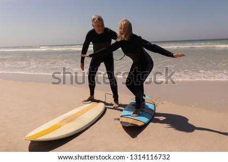 Zijaanzicht senior vrouwelijke surfer surfboard permanente Stockfoto © wavebreak_media