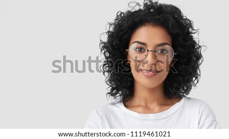 Close up shot of dark haired pretty woman wears eyewear, has serious expression at camera, poses aga Stock photo © vkstudio