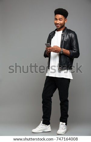 Image of african american guy in jacket smiling and holding cell Stock photo © deandrobot