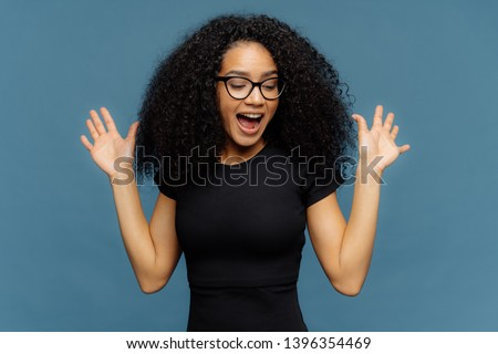 Slim overemotive dark skinned woman raises hands, opens mouth, gestures actively from positive emoti Stock photo © vkstudio