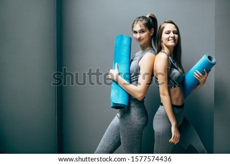 Cheerful young fitness lady holding fitness rug. Stock photo © deandrobot