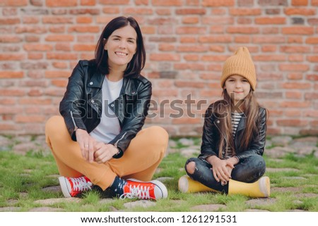 Horizontal shot of restful mother and daughter sit in lotus pose, wears fashionable leather jackets, Stock photo © vkstudio