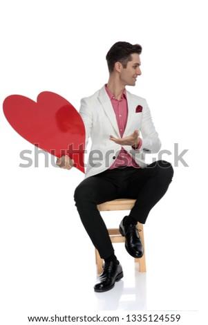 ülő boldog elegáns férfi bemutat piros Stock fotó © feedough