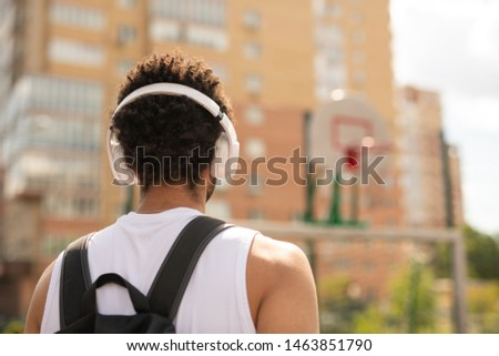 Rear view of young intercultural sportsman with headphones and backpack Stock photo © pressmaster