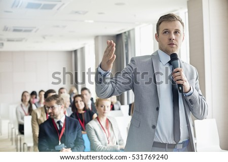 Stock photo: Businesswoman public speaking on microphone in office