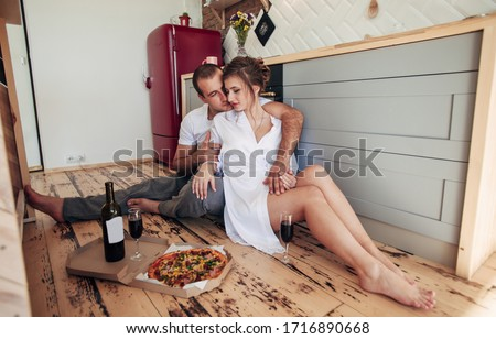 happy young couple eating pizza at the kitchen stock photo © lopolo