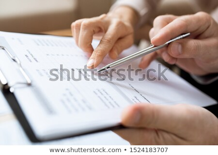 One of humans holding pen over paper while discussing financial expenses Stock photo © pressmaster