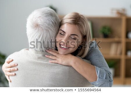 Happy young affectionate woman with toothy smile giving hug to her senior father Stock photo © pressmaster