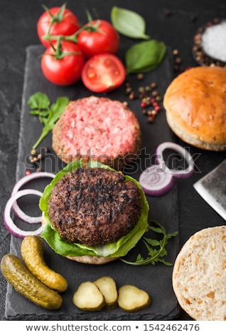 Fresh grilled and raw minced pepper beef burger on stone chopping board with buns onion and tomatoes Stock photo © DenisMArt