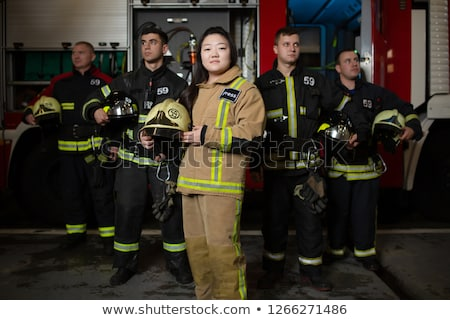 Team of fire fighters looking into camera Stock photo © Kzenon
