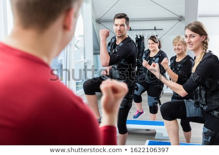 Fit senior lady and young man in ems gym Stock photo © Kzenon