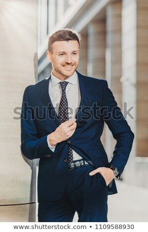 Vertical shot of handsome male with appealing appearance, dressed in formal black suit, keeps hand i Stock photo © vkstudio