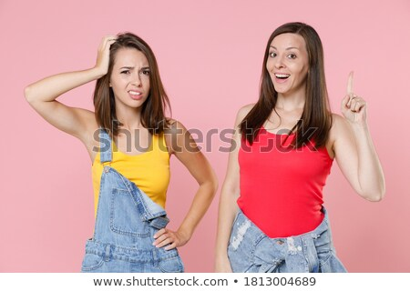 Portrait of two confused women looking at camera and pointing fingers Stock photo © deandrobot
