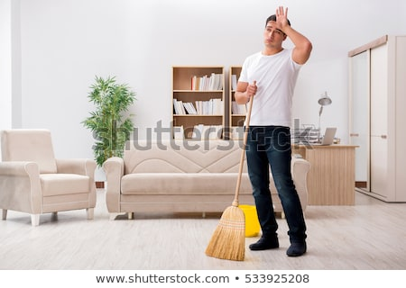 man with broom cleaning floor at home Stock photo © dolgachov