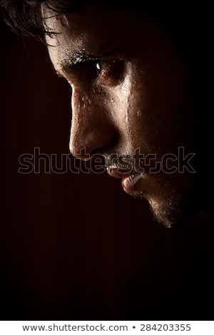 Young Indian angry man sweating over dark stock photo © ziprashantzi